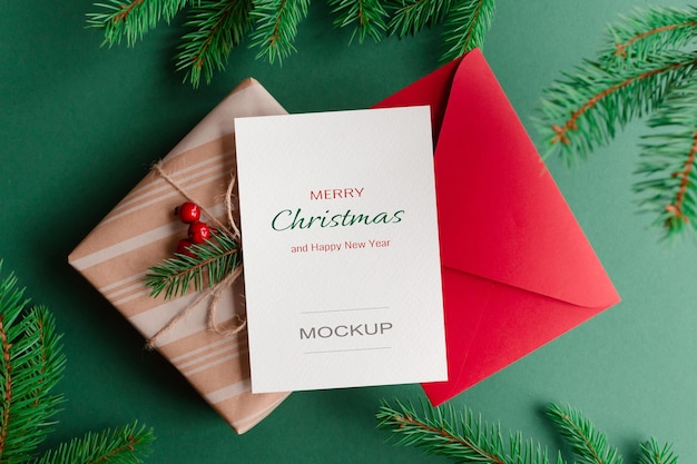 Christmas greeting card mockup with red envelope, gift box and green fir tree branches