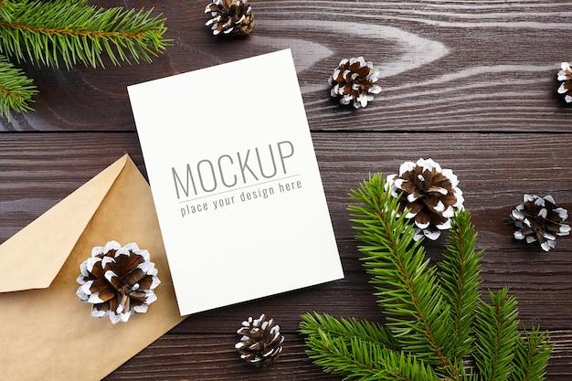 木製の装飾、コーン、モミの木の枝とクリスマスグリーティングカードのモックアップ