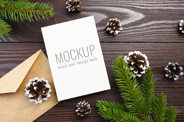Christmas greeting card mockup with wooden decorations, cones and fir tree branches