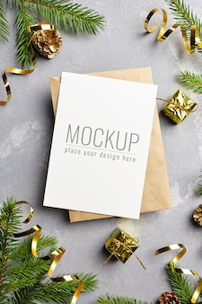 Christmas greeting or invitation card mockup with envelope, pine cones decorations and fir tree branches