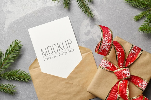 封筒、ギフトボックス、モミの木の枝とクリスマスの挨拶または招待カードのモックアップ