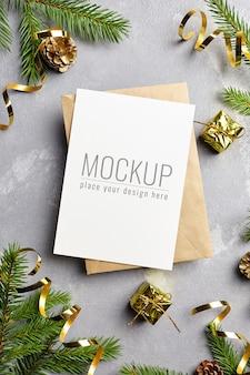 封筒、松ぼっくりの装飾、モミの木の枝とクリスマスの挨拶または招待状のモックアップ