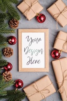 Рождественские праздники композиция с фоторамкой макет. красные фенечки, подарки и еловые ветки.