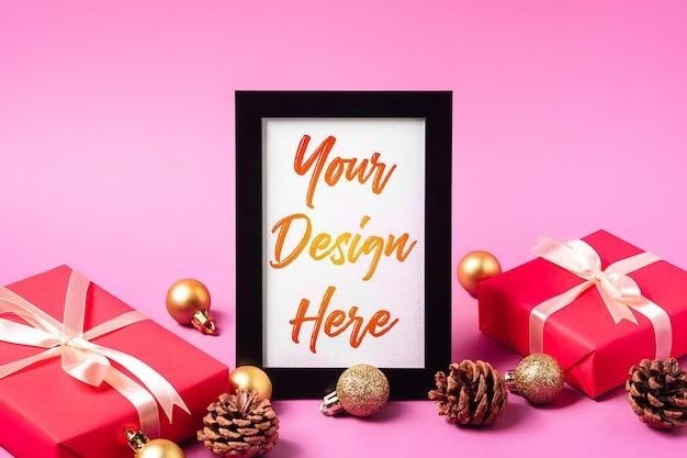 空の額縁とクリスマスの最小限の構成。金色の飾り、ギフトボックス、松ぼっくりの飾り。グリーティングカードテンプレートのモックアップ
