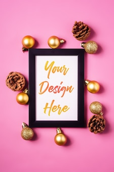 Christmas minimal composition with empty picture frame with golden ornaments and pine cones d