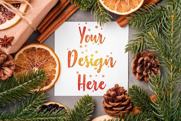 クリスマスのモックアップ構成。ギフトボックス、シナモン、アニス、ドライフルーツ、松ぼっくり、灰色の背景にモミの針の装飾