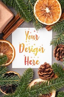 Рождественский макет композиции с подарочной коробкой, корицей, анисом, сухофруктами, сосновыми шишками и украшениями из хвои на сером