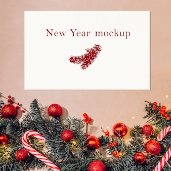 Рождественский макет, открытка на столе с еловыми ветками, красными шариками, ягодами и леденцами
