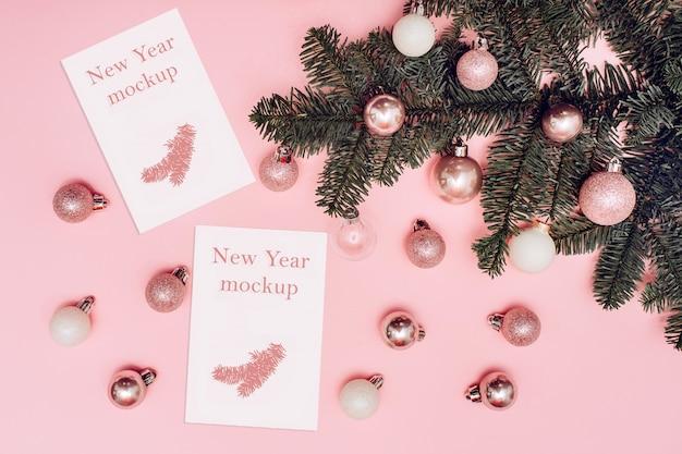 クリスマスのモックアップ、ピンクの背景に白とピンクのボール、テキスト用の白いカードとスプルースの枝