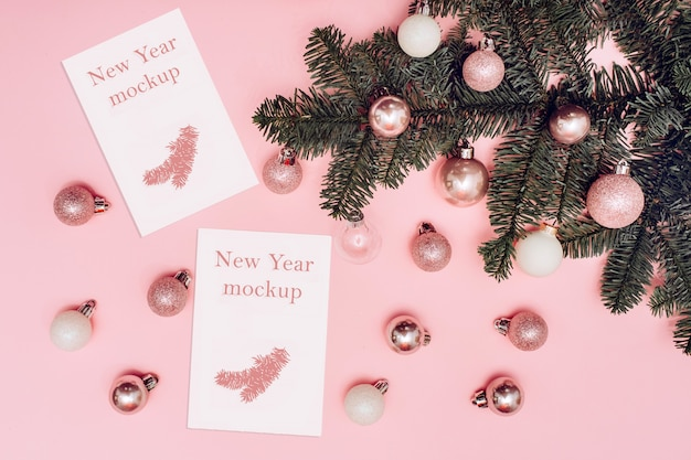 Christmas mockup, spruce branch with white and pink balls on a pink background, white card with place for text