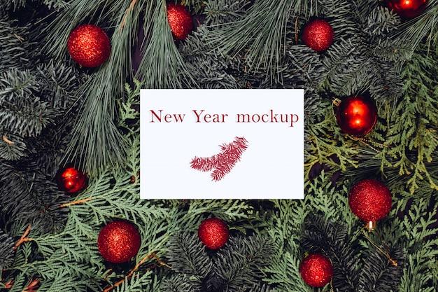 Рождественский макет, белый лист бумаги, лежащий на еловых ветвях, красные елочные шары.