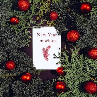 クリスマスのモックアップ、小ぎれいなな枝、赤いクリスマスボールの上に横たわる紙の白いシート。 Premium Psd