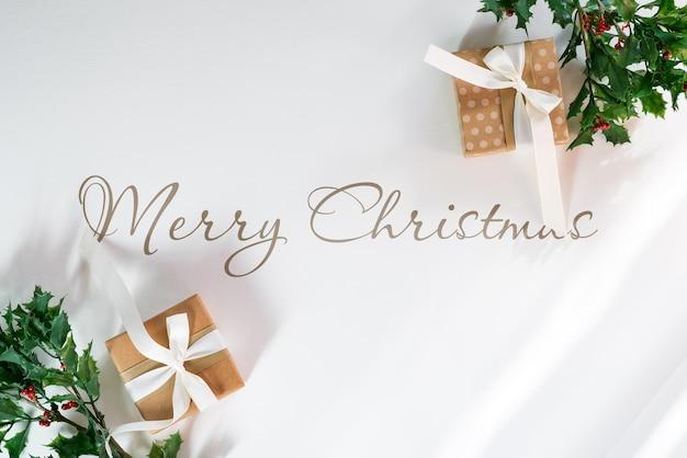 ギフトボックスとヒイラギの枝とクリスマスのモックアップ