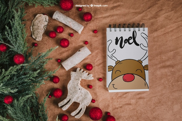 Christmas mockup with notepad next to balls and reindeer