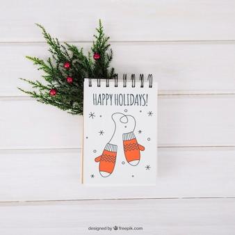 Christmas mockup with notepad on mistletoe branch