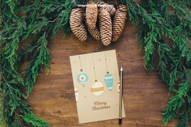 Рождественский макет с сосновыми шишками и поздравительной открыткой