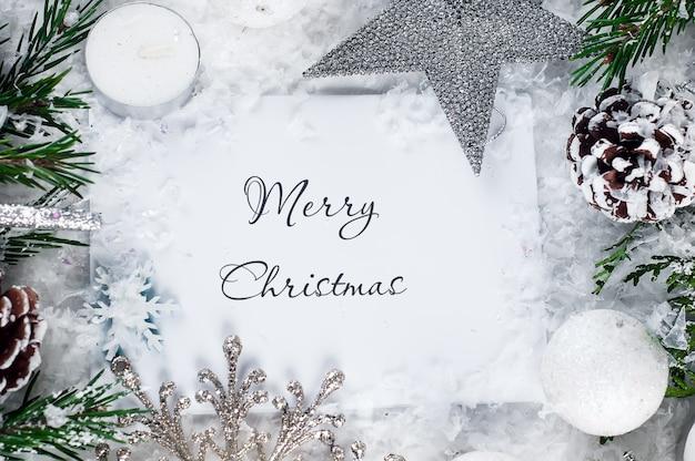 雪、モミの枝や装飾品とクリスマスのモックアップ