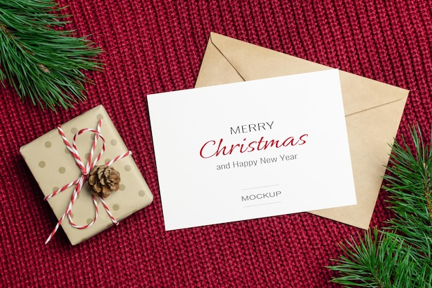 Christmas or new year greeting card mockup with decorated gift box and pine tree branches