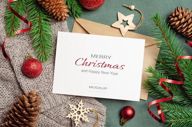 Christmas or new year greeting card mockup with envelope and festive decorations with fir tree branches