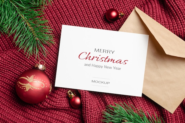 Christmas and new year greeting card mockup with envelope and red balls decorations with pine tree branches