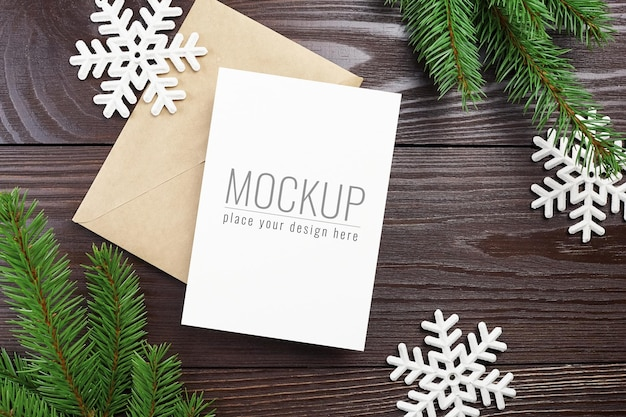 Christmas or new year greeting card mockup with envelope, white snowflakes and fir tree branches