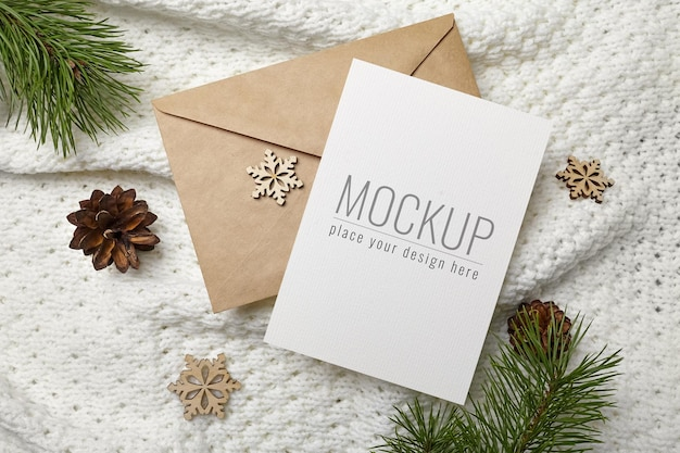 Christmas or new year greeting card mockup with envelope, wooden decorations and pine tree branches with cones