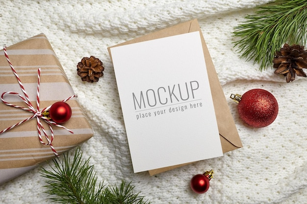 Christmas or new year greeting card mockup with gift box, festive decorations and pine tree branches