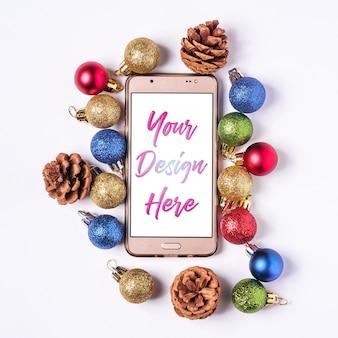 クリスマスのオンラインショッピング。白い空白の画面でスマートフォンのモックアップ。カラフルなボールと松ぼっくりの装飾。