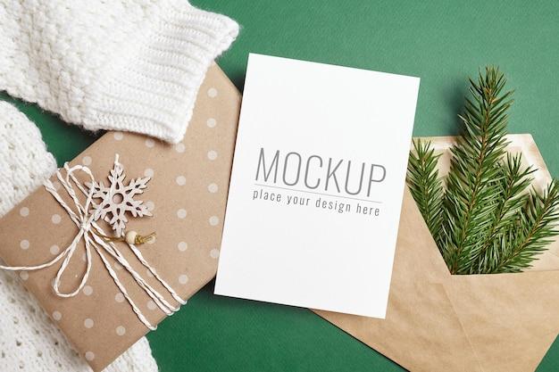 装飾されたギフトボックスとモミの木の枝が付いているクリスマスまたは新年のグリーティングカードのモックアップ