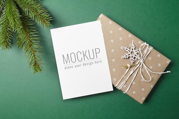 装飾されたギフトボックスと緑のモミの木の枝とクリスマスまたは新年のグリーティングカードのモックアップ