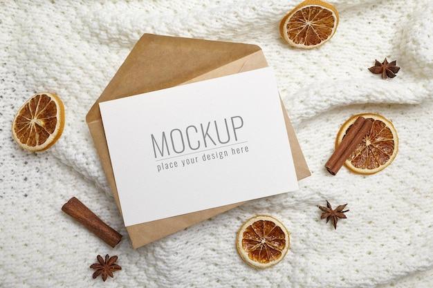 ニットの背景にドライオレンジとクリスマスまたは新年のグリーティングカードのモックアップ