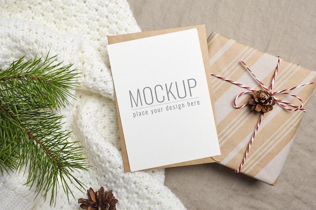 クリスマスまたは新年のグリーティングカードのモックアップ、封筒、ギフトボックス、コーン付き松の木の枝