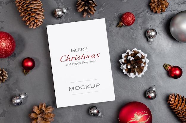 크리스마스 또는 새해 인사말 카드 모형에는 축제 장식과 원뿔이 어둠에 깔려 있습니다.