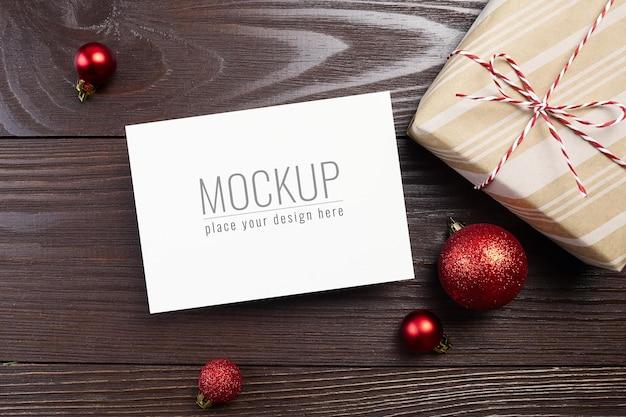 ギフトボックスと赤いボールの装飾が施されたクリスマスまたは新年のグリーティングカードのモックアップ