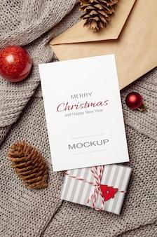 Макет рождественской или новогодней поздравительной открытки с подарочной коробкой, конусами, конвертом и праздничными украшениями