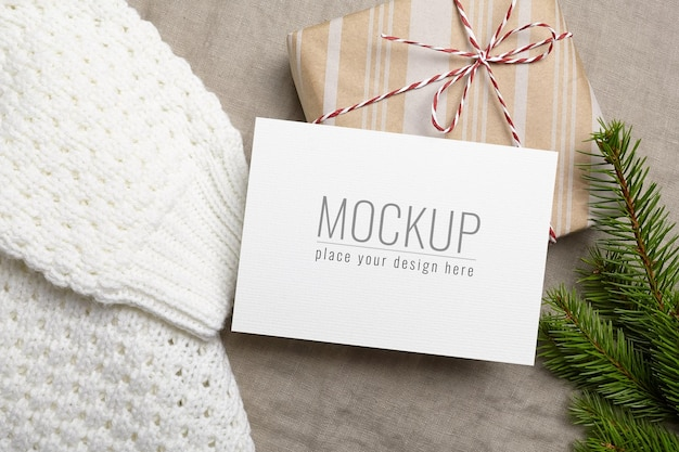 クリスマスまたは新年のグリーティングカードのモックアップ、ギフトボックス、ニットセーター、モミの木の枝