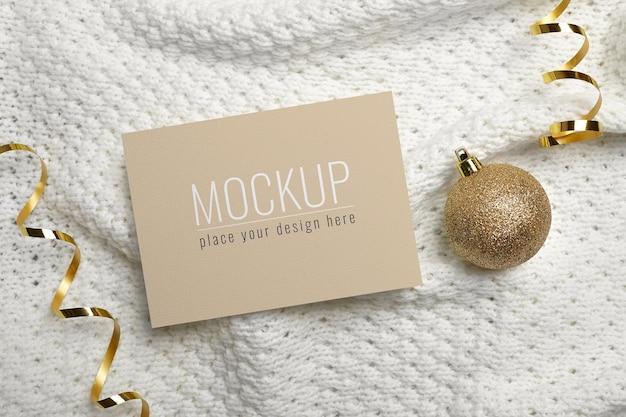 ニットの背景に金のボールの装飾が施されたクリスマスまたは新年のグリーティングカードのモックアップ
