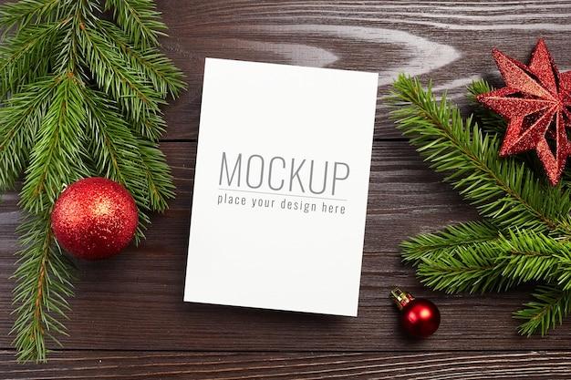 赤いお祭りの装飾とモミの木の枝とクリスマスまたは新年のグリーティングカードのモックアップ