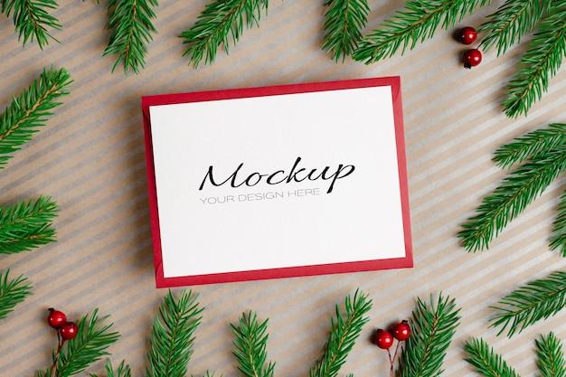 クリスマスまたは新年の挨拶または封筒とモミの木の枝と招待状のモックアップ
