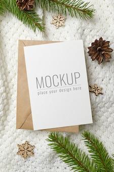 クリスマスまたは新年の挨拶または招待カードのモックアップ、封筒、木製の装飾、モミの木の枝