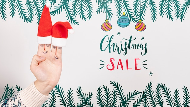 Christmas sale with santa's hat on a hand