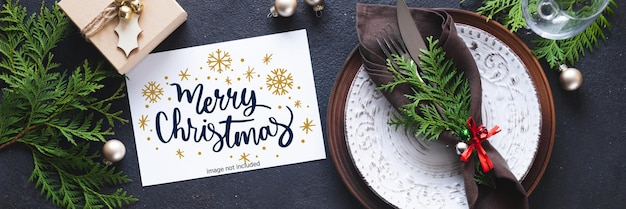 Christmas table setting with mockup of greeting card or invitation.
