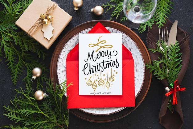 グリーティングカードまたは招待状のモックアップとクリスマステーブルの設定。