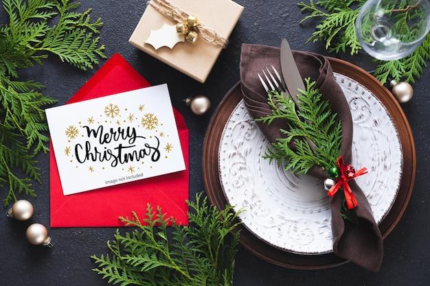 Сервировка рождественского стола с макетом поздравительной открытки или приглашения.