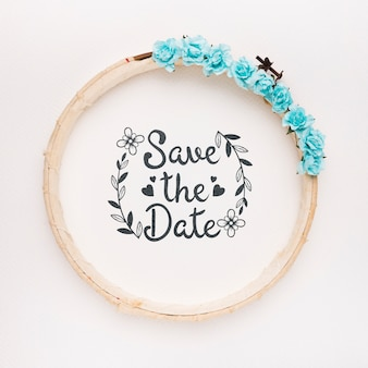 Circular wooden frame with blue roses save the date mock-up