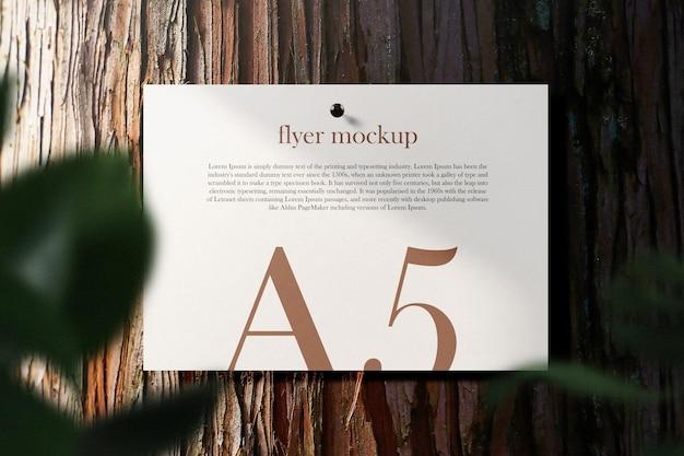 葉のある樹皮の木のテーブルの最小限のa5チラシモックアップピンをきれいにします。