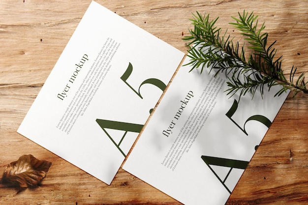 Clean minimal a5 flyer mockup on wood table with leaves.