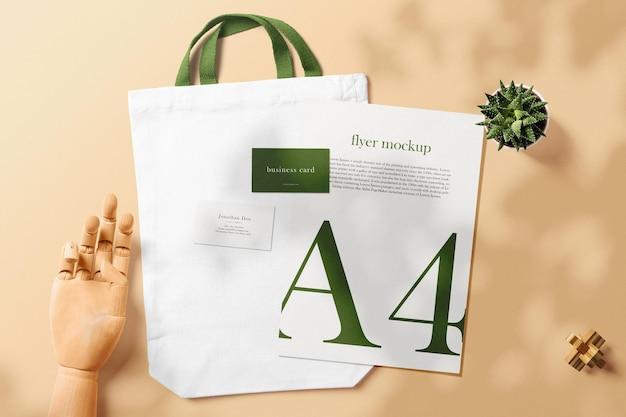 植物と木の手でバッグの最小限の名刺とa4モックアップをきれいにする