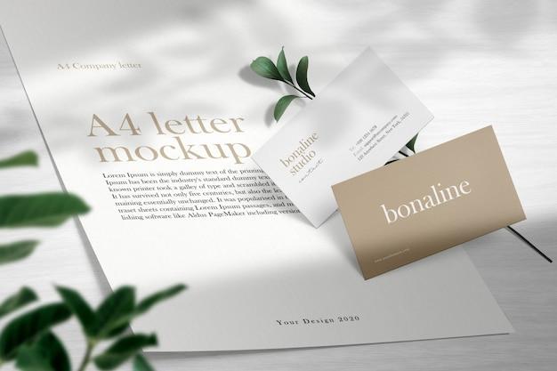 나무 바닥과 빛 그림자에 최소한의 비즈니스 카드와 편지 a4 모형을 청소하십시오.