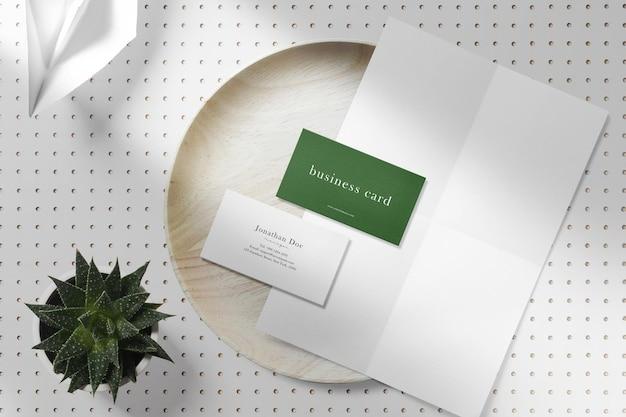 植物と木の板に最小限の名刺と白い紙のモックアップをきれいにする